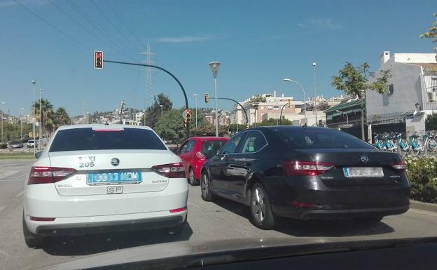 Imagen de archivo de un taxi y un VTC del mismo modelo en un semáforo de la capita malagueñal./SUR